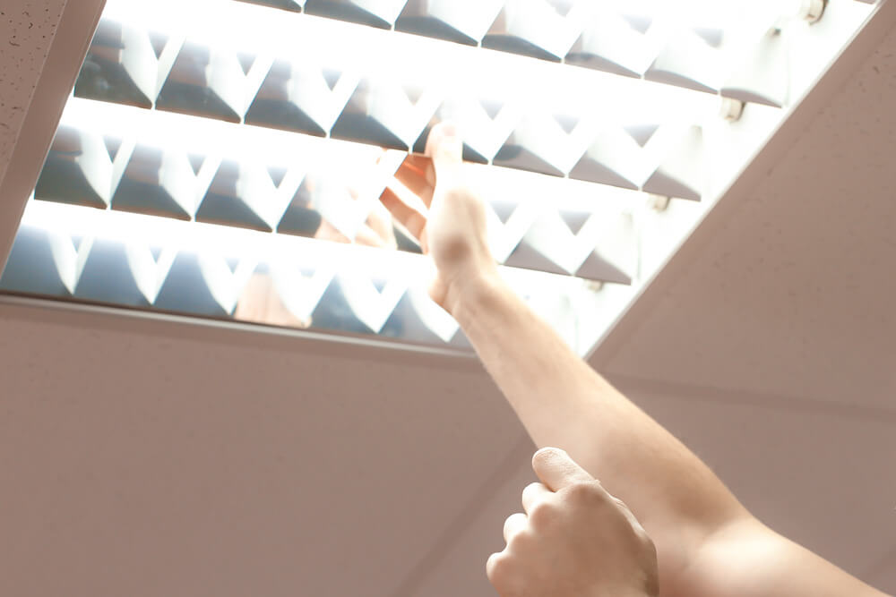 Electrician's hand reaching into fluorescent interior lighting fixture to perform maintenance.