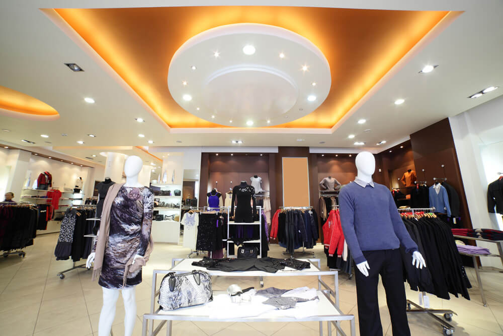 Commercial retail display with mannequins, clothing racks, and a large sculptural interior lighting fixture in the ceiling framed with warm recessed lighting.