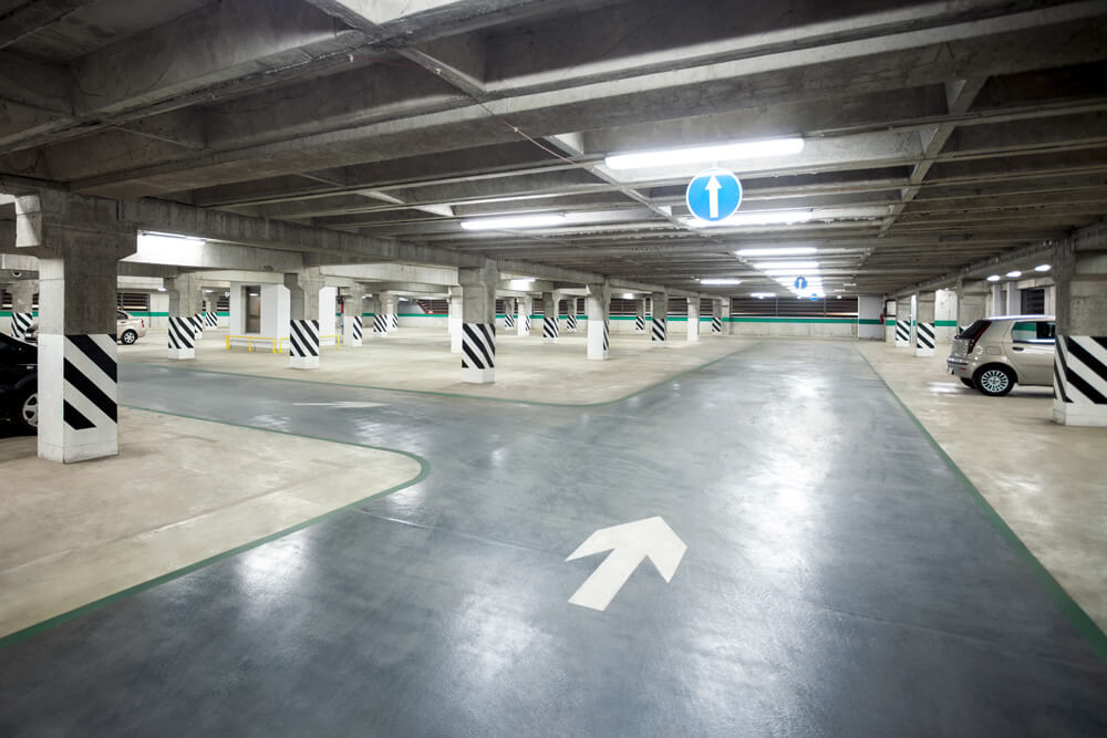 Indoor parking garage lighting illuminates an exit aisle with two cars in parking spots and reflective tape on parking garage columns.