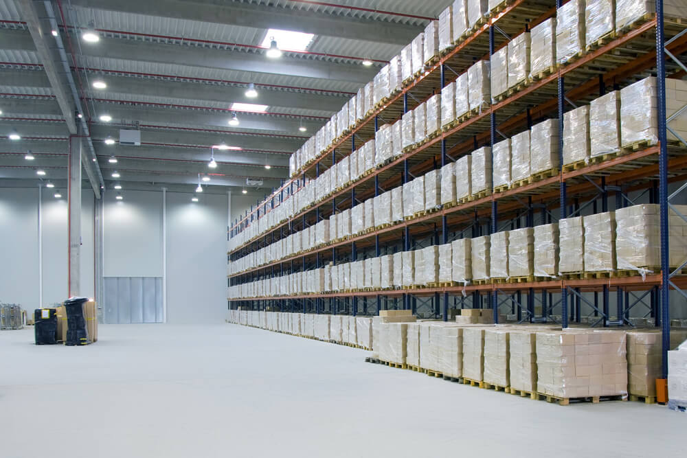 Large aisle with shelves of pallets and high industrial ceilings with bright warehouse lighting fixtures.