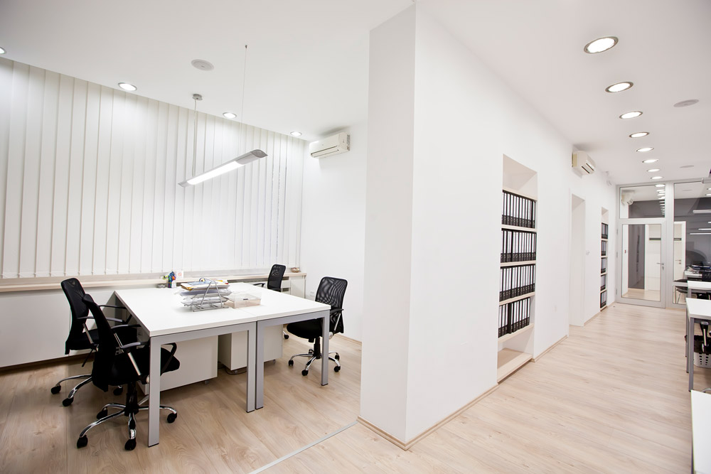 Office suite and conference room with light hardwood floors and white walls illuminated by led lighting.
